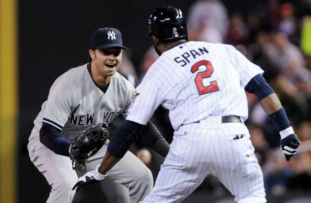 Minnesota Twins' Denard Span tries to avoid New York Yankees first baseman Nick Swisher, left, but to no avail as Swisher made the tag after fielding Span's short infield grounder in the fifth inning of a baseball game Tuesday, Sept. 25, 2012, in Minneapolis. (AP Photo/Jim Mone) Photo: Jim Mone