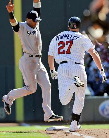 New York Yankees second baseman Robinson Cano, left, jumps onto first for the out after taking the throw from pitcher CC Sabathia on an infield grounder by Minnesota Twins' Chris Parmelee, right, during the second inning of a baseball game, Wednesday, Sept. 26, 2012 in Minneapolis. (AP Photo/Jim Mone) Photo: Jim Mone