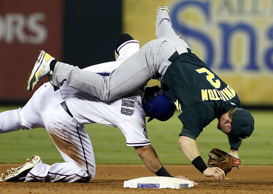 Oakland Athletics shortstop Cliff Pennington (2) is upended by Texas Rangers' Mitch Moreland after Moreland was forced at second on a double play in the fourth inning of a baseball game, Wednesday, Sept. 26, 2012, in Arlington, Texas. The Rangers' Ian Kinsler was out at first. (AP Photo/Tony Gutierrez) Photo: Tony Gutierrez, Associated Press