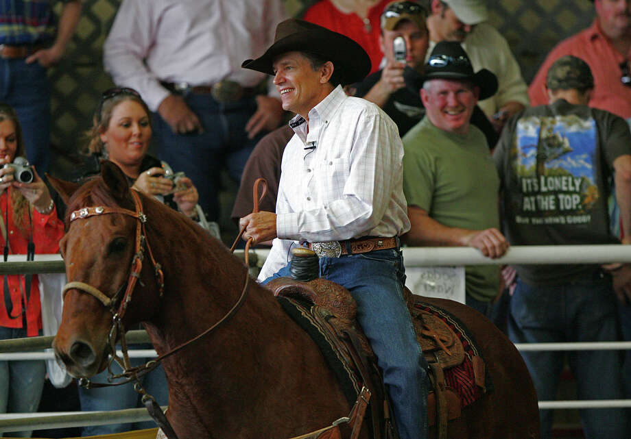 FILE - Country singer George Strait gets spectators at the 2006 George Strait Team Roping Classic held at the San Antonio Rose Palace in Leon Springs, Texas on Saturday, Mar. 11, 2006. Strait is closing and selling the San Antonio Rose Palace after 20 years of ownership. Photo: KIN MAN HUI, SAN ANTONIO EXPRESS-NEWS / SAN ANTONIO EXPRESS-NEWS