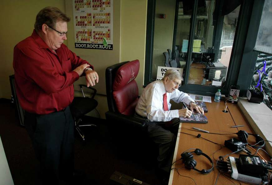 Lowell Matheny, Astros radio production broadcast engineer, checks his watch to remind Milo Hamilton