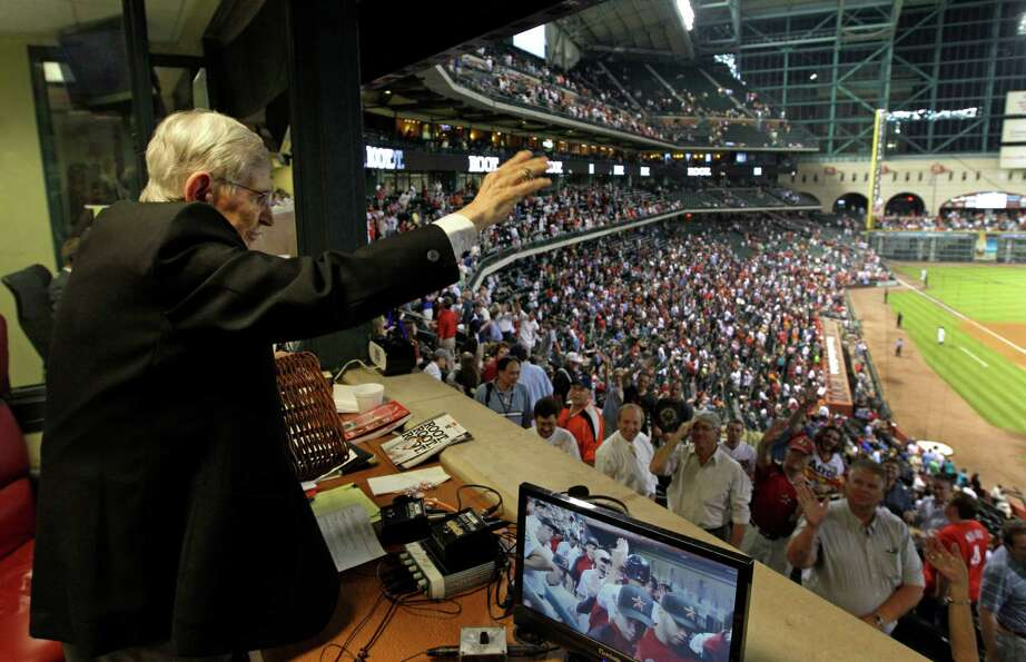 Milo Hamilton waves to the crowd from the radio booth in the 7th inning as he calls the Houston Astr