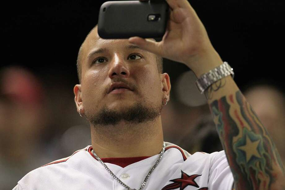 A fan takes a photo of the video screen as Milo Hamilton addressed the crowd during the seventh inning stretch of an MLB baseball game at Minute Maid Park on Wednesday, Sept. 26, 2012, in Houston. Photo: Karen Warren, Houston Chronicle / © 2012  Houston Chronicle