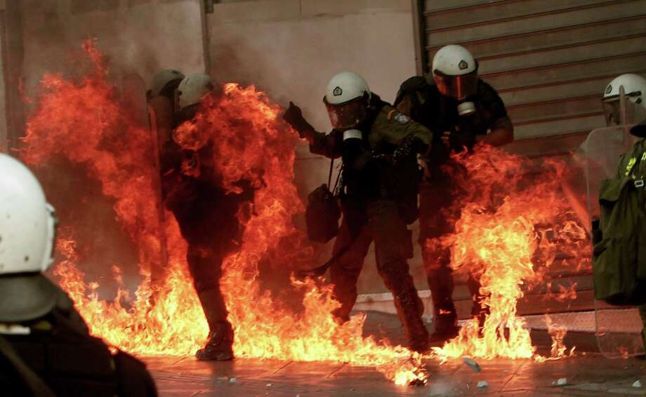 A fire bomb explodes among riot police during a nationwide general strike in Athens, Wednesday, Sept. 26, 2012. Police clashed with protesters hurling petrol bombs and bottles in central Athens Wednesday after an anti-government rally called as part of a general strike in Greece turned violent. (AP Photo/Nikolas Giakoumidis) Photo: Nikolas Giakoumidis