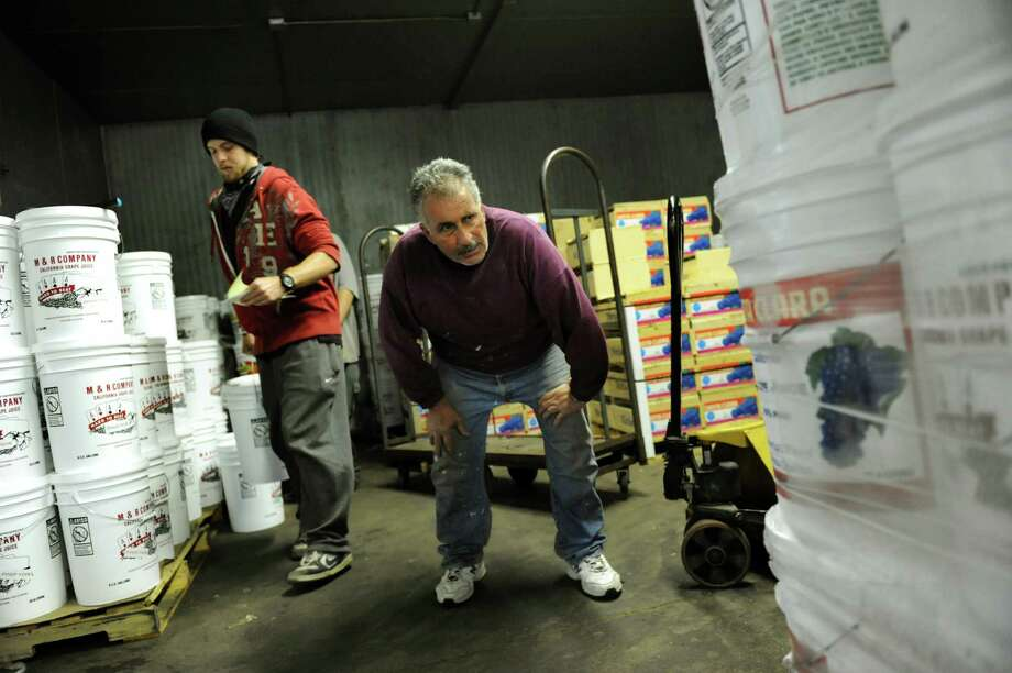 """Joseph """"Pino"""" Rizzo of Guilderland, center, looks for the juice he ordered to mix in with his crushed grapes on Wednesday, Sept. 26, 2012, at Ryan's Farmer's Market in Albany, N.Y. (Cindy Schultz / Times Union) Photo: Cindy Schultz / 00019413A"""