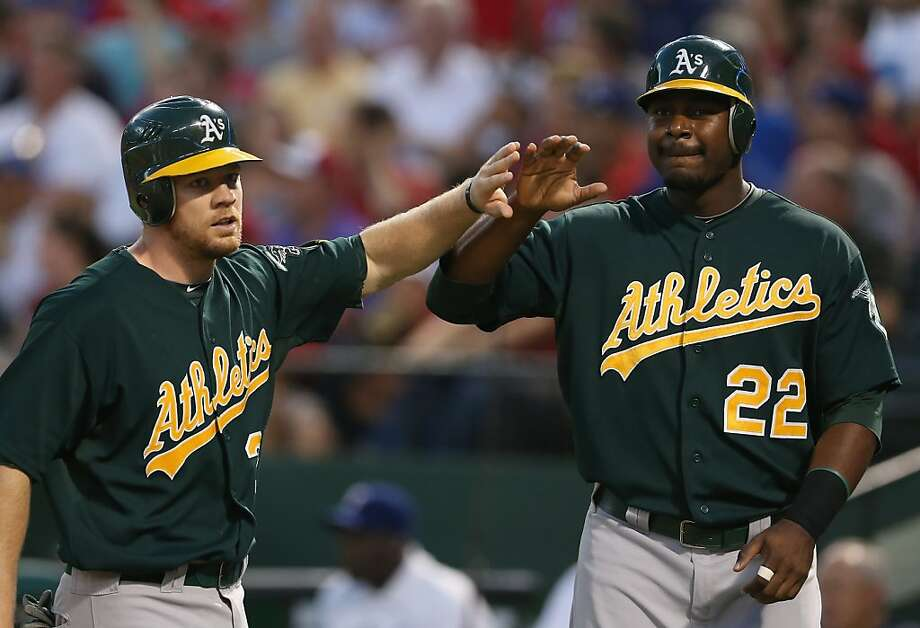 Brandon Moss (left) glad-hands Chris Carter after they scored first-inning runs in the A's second straight win. Photo: Ronald Martinez, Getty Images