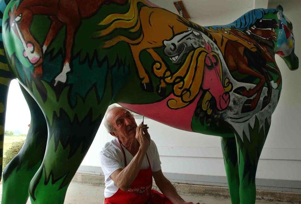 Artist Pierre Bellocq, paints a full-size fiberglass horse at Stone Bridge Farm in Schuylerville, N.Y., Monday July 21, 2003. (Paul Buckowski / Times Union archive)