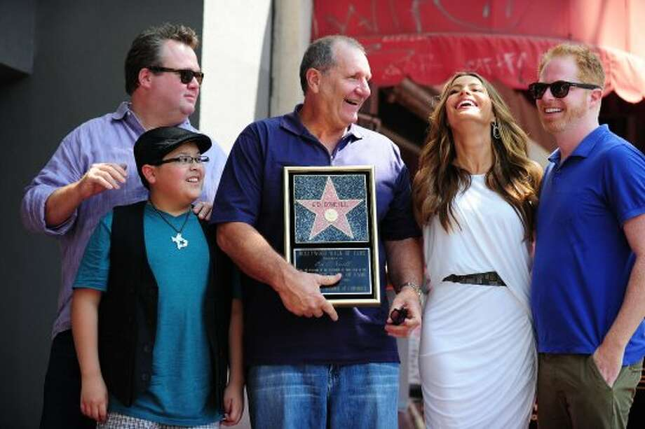 "Ed O'Neill (C), with his ""Modern Family"" co-stars, actors Eric Stonestreet (L), Rico Rodriguez (2L) and Sofia Vergara (2R) and Jesse Tyler Ferguson (R), being honored with Hollywood Walk of Fame star in 2011.  (ROBYN BECK / AFP/Getty Images)"