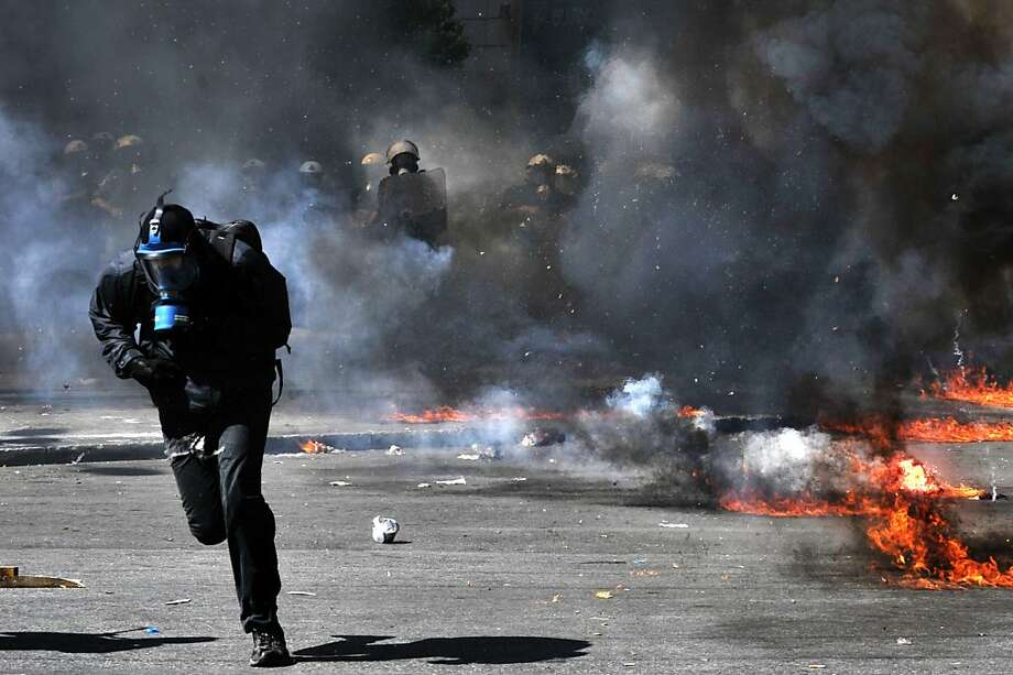 A protester runs from riot police during a 24-hours general strike in Athens on September 26, 2012. Greece's two main labour unions hold a 24-hour general strike to protest against a new austerity package, which the country's EU and International Monetary Fund creditors have said is necessary for Athens to receive the next installment from its rescue loans. Nearly 34,000 people marched in Athens and another 18,000 in Thessaloniki, according to the police, in the first general strike to be held since the new government took office in June, bringing the country to a standstill. Photo: Louisa Gouliamaki, AFP/Getty Images
