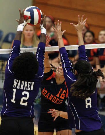 Brandeis' Cassidy Acord (12) hits into Warren blockers Laycia Robinson (12) and Lauren Bernal (08) in high school volleyball at Taylor Fieldhouse on Wednesday, Sept. 26, 2012. Photo: Kin Man Hui, San Antonio Express-News / ©2012 San Antonio Express-News