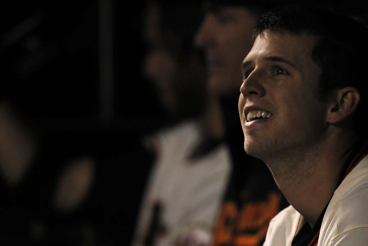 Buster Posey smiles in the dugout after his 100th rbi in the third inning. The San Francisco Giants played the Arizona Diamondbacks at AT&T Park in San Francisco, Calif., on Wednesday, September 26, 2012, defeating the Diamondbacks 6-0