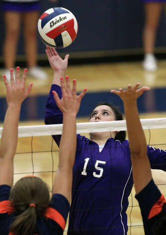 Warren's Shaina Garza (15) taps a shot over Brandeis blockers to make the winning point to take game 2 in high school volleyball at Taylor Fieldhouse on Wednesday, Sept. 26, 2012. Photo: Kin Man Hui, San Antonio Express-News / ©2012 San Antonio Express-News
