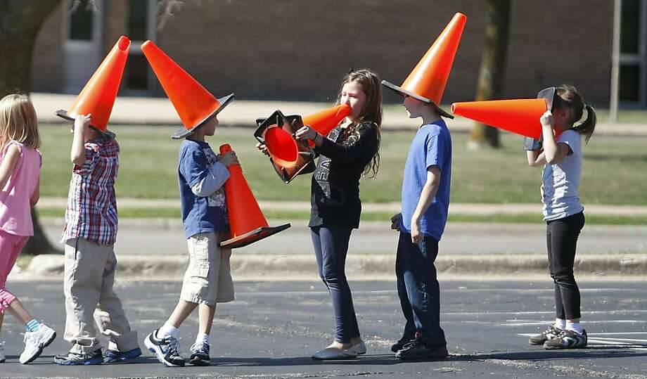 Children of the cone: The pylon detail at Dubuque Lutheran School in Dubuque, Iowa, gets a little sidetracked while setting up cones for a footrace. Photo: Jeremy Portje, Associated Press
