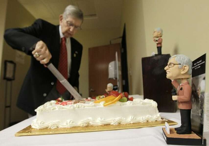 Milo Hamilton bobbleheads are displayed as he cuts and passes out pieces of his cake in the media di