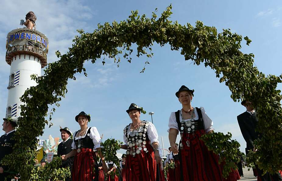 Visitors wearing traditional Bavarian clothes take part in the costumes and riflemen parade at the T
