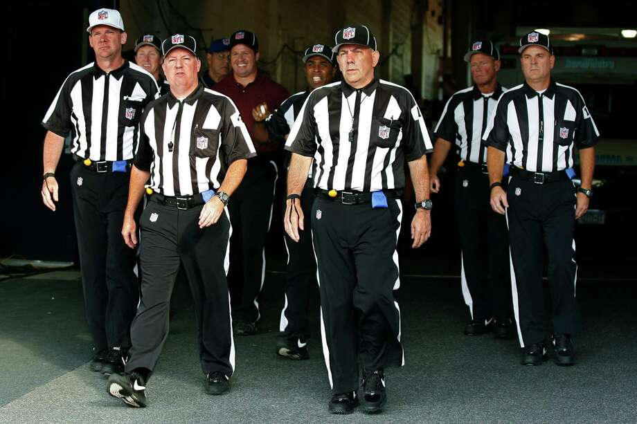FILE - In this Aug. 9, 2012, file photo, officials walk towards the field for an NFL football game between the Buffalo Bills and the Washington Redskins in Orchard Park, N.Y. The NFL and referees' union reached a tentative agreement on Wednesday, Sept. 26, to end a three-month lockout that triggered a wave of frustration and anger over replacement officials and threatened to disrupt the rest of the season. (AP Photo/Bill Wippert, File) Photo: Bill Wippert