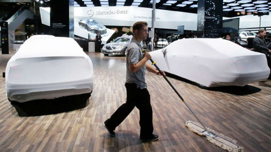 Worker cleans the floor next to Mercedes cars in preparation for the upcoming Auto Show in Paris, Wednesday, Sept. 26, 2012. The Paris Auto Show opens to the public Saturday Sept. 29 until Oct. 14, 2012. Europe�s carmakers could be forgiven for worrying that the slogan for this year�s Paris Auto Show, �The Future, Now�, is a threat of more gloom and hardship to come than a promise of more prosperous times. Photo: Michel Euler, . / AP