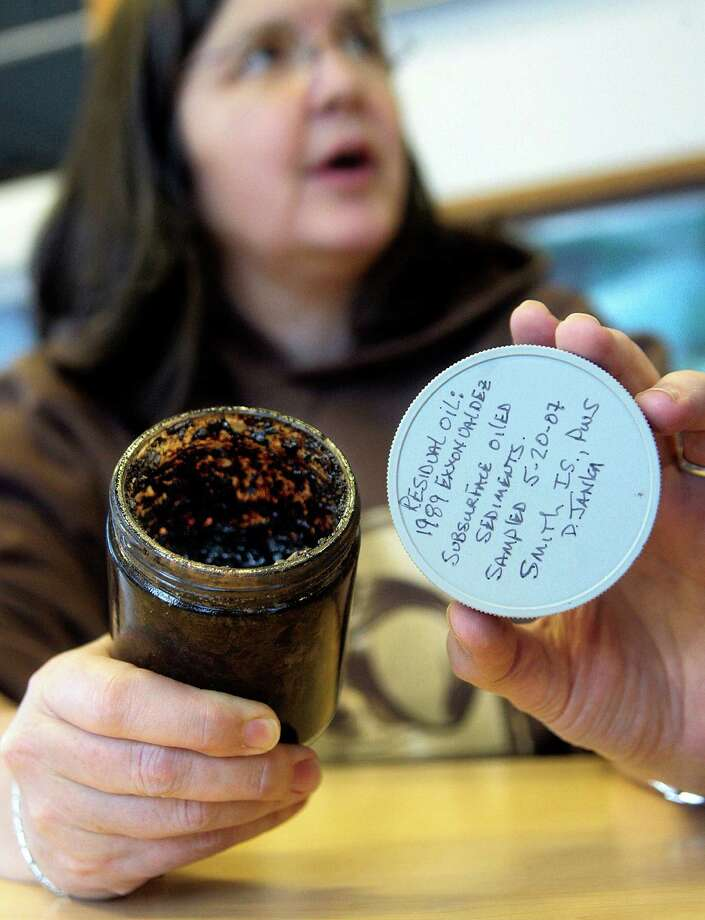 Nancy Bird shows oil-soaked soil collected in May 2007 from Smith Island in Prince William Sound, on display at the Prince William Sound Science Center in Cordova, Alaska. With the 20th anniversary of the Exxon Valdez oil spill nearing, she said Scientists tell me the remaining oil will take decades and possibly centuries to disappear. Photo: Al Grillo, AP / AP