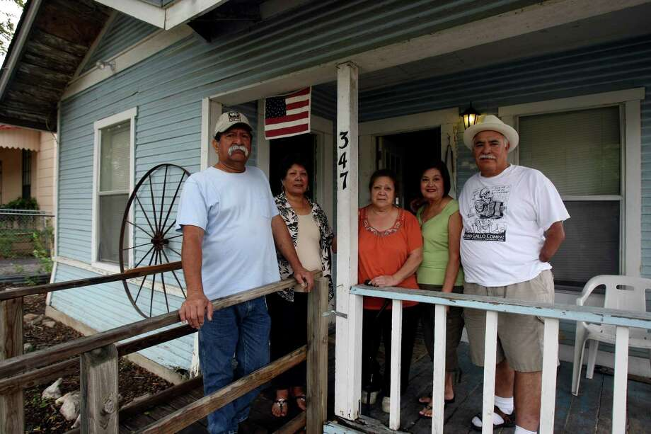 Members of the Lopez family stand on the front porch of 347 Everest. The home is in El Barrio Escondido, a tiny remnant of a hidden neighborhood located just north of Alamo Heights left over from the Cementville days. Many of the residents came to work on the ranch or at the church that serviced Cementville workers, or moved there because they liked living outside of the city. Photo: Helen L. Montoya, Helen Montoya/Conexión / ©SAN ANTONIO EXPRESS-NEWS