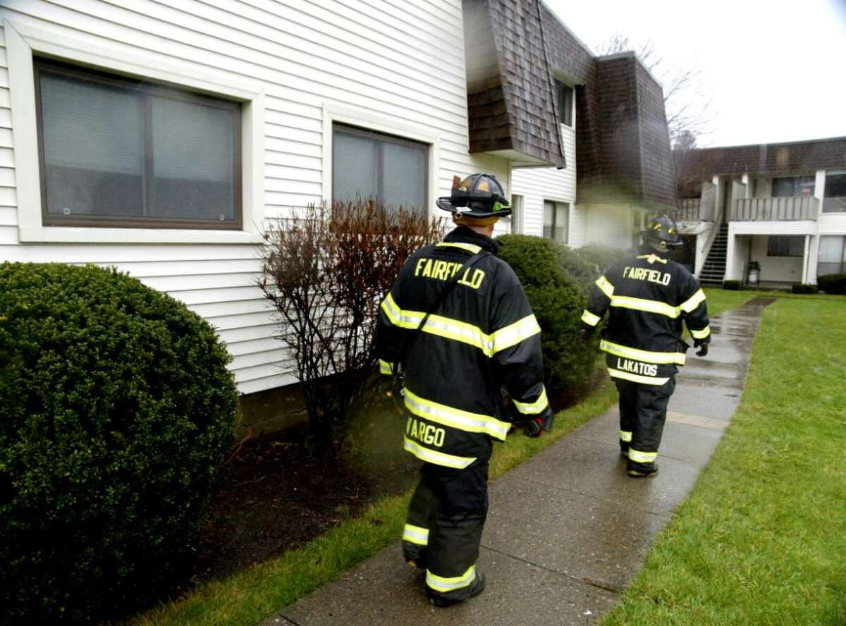 Fairfield firefighters Ron Vargo and John Lakatos go door to door at the Quincy Condos in Fairfield, checking damage at condos after an overnight fire on Weds. Dec. 9, 2009.