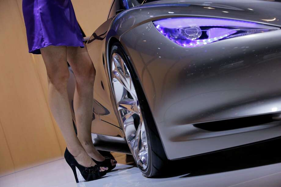 A hostess poses next to a Mazda Infiniti Emerg-e during the press day at the Paris Auto Show, France, Thursday, Sept. 27, 2012. The Paris Auto Show will open its gates to the public from Sept. 29 to Oct. 14. (AP Photo/Christophe Ena) Photo: Christophe Ena, Associated Press / AP