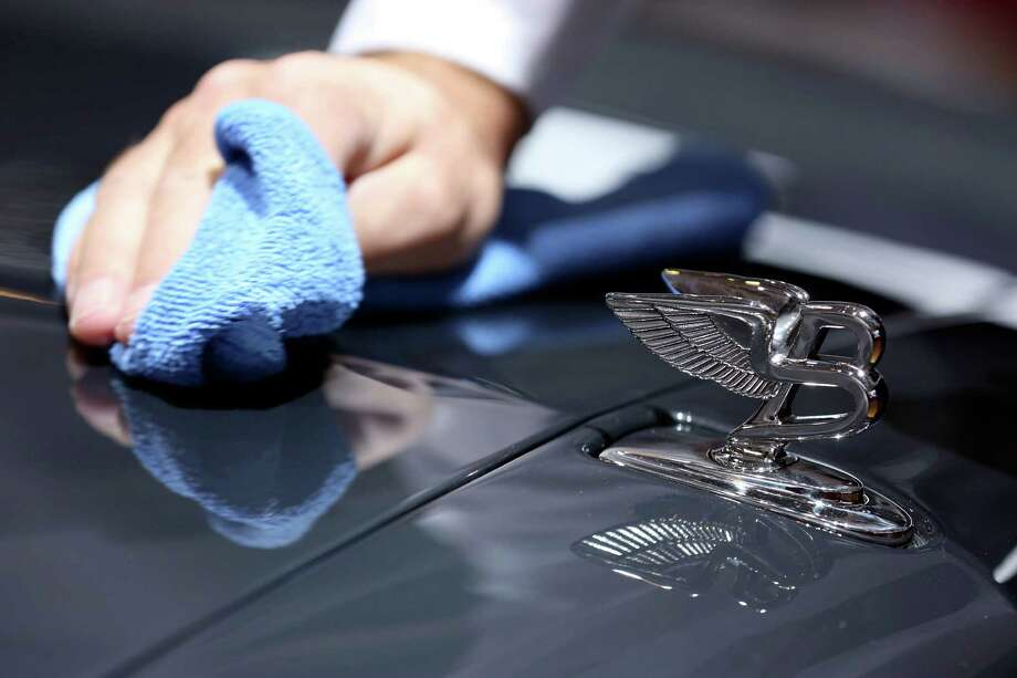 An employee polishes the hood of a Bentley Mulsanne automobile, produced by Bentley Motors Ltd., on the first day of the Paris Motor Show in Paris, France, on Thursday, Sept. 27, 2012. The Paris Motor Show will showcase the latest models from the auto industry's leading manufacturers at the Paris Expo exhibition centre this week. Photographer:  Photographer: Jason Alden/Bloomberg Photo: Jason Alden, Bloomberg / Copyright 2012 Bloomberg Finance LP