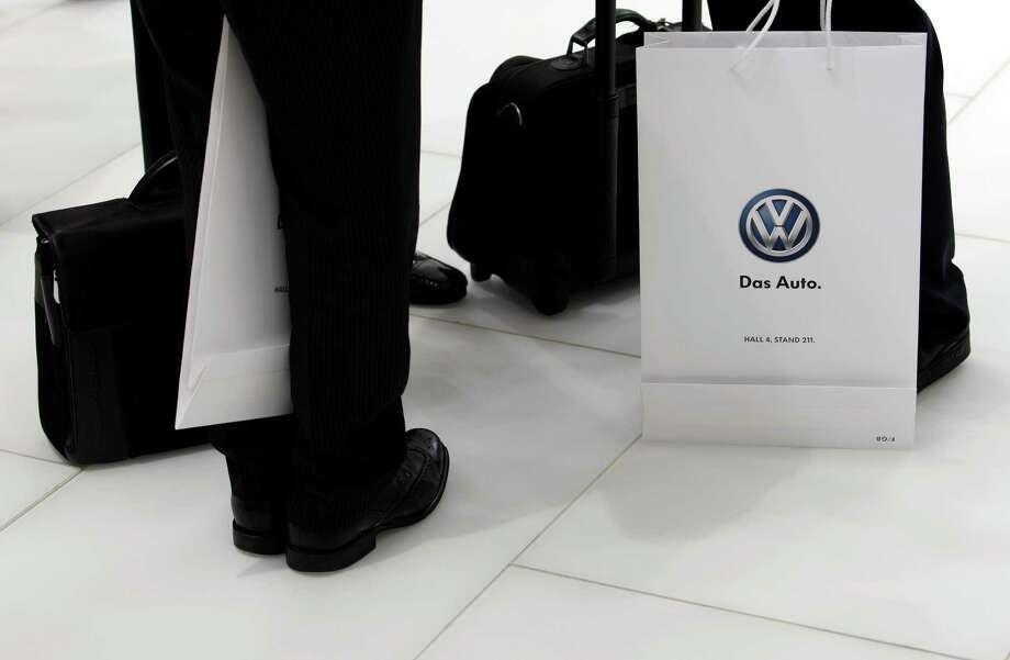 Visitors stand with Volkswagen AG (VW) branded bags on the first day of the Paris Motor Show in Paris, France, on Thursday, Sept. 27, 2012. The Paris Motor Show will showcase the latest models from the auto industry's leading manufacturers at the Paris Expo exhibition centre this week. Photographer: Photographer: Balint Porneczi/Bloomberg Photo: Balint Porneczi, Bloomberg / Copyright 2012 Bloomberg Finance LP