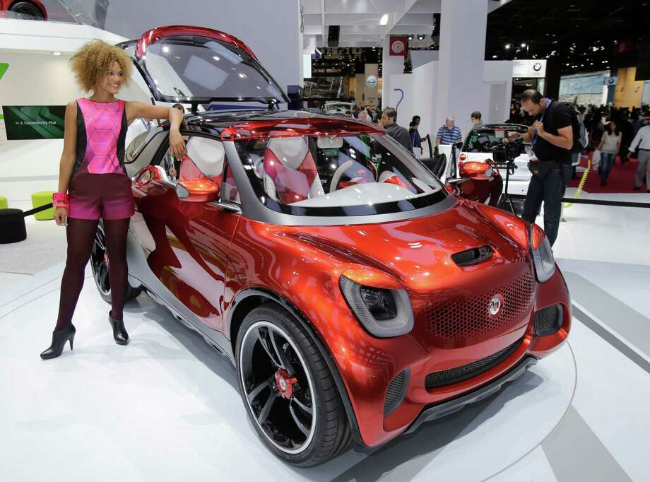A hostess poses next to a Smart forstars, an electric concept car, during the press day at the Paris Auto Show, France, Thursday, Sept. 27, 2012. The Paris Auto Show will open its gates to the public from Sept. 29 to Oct. 14. (AP Photo/Michel Euler) Photo: Michel Euler, Associated Press / AP