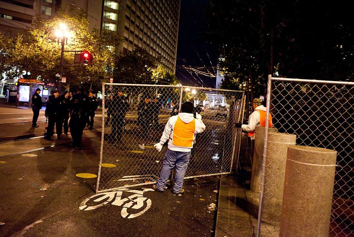 DPW places a chain-link fence around the perimeter during an unannounced midnight raid on the Occupy encampment at 101 Market Street in San Francisco, Calif., Wednesday, September 26, 2012.