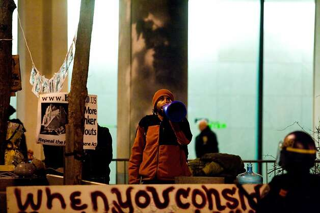 A man at the Occupy encampment shouts through a megaphone during an unannounced midnight raid on the Occupy encampment at 101 Market Street in San Francisco, Calif., Wednesday, September 26, 2012. Photo: Jason Henry, Special To The Chronicle