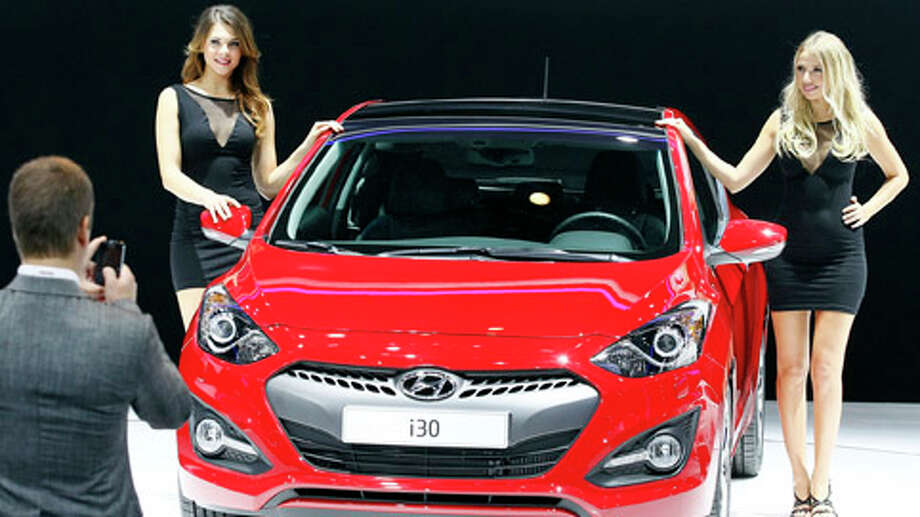 Hostesses pose next to a Hyundai i30 family car during the press day at the Paris Auto Show, France, Thursday, Sept. 27, 2012. The Paris Auto Show will open its gates to the public from Sept. 29 to Oct. 14. Photo: Michel Euler, . / AP