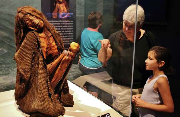 This young woman with long, black hair was naturally mummified in the warm desert air, seated in the burial position typical in Chile before 1400 A.D. She was wrapped in fabric after her death, the impression of which is still visible on her chin and cheeks. She has unusual tattoos; an oval with a dot inside on both breasts and beneath the left corner of her mouth. Little is known about the meaning of these mysterious tattoos. Photo: Darryl Moran, Courtesy