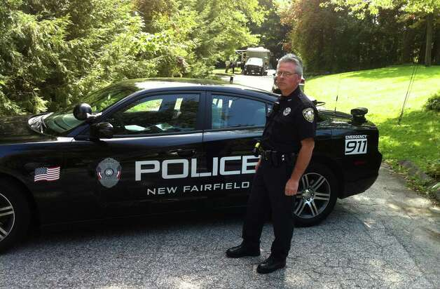 New Fairfield Police officer Michael Corrigan is on the scene of a fatal shooting on Meeting House Hill Circle. Sources say a man shot his son, who was allegedly breaking into his aunt's house. Photo: Carol Kaliff / The News-Times