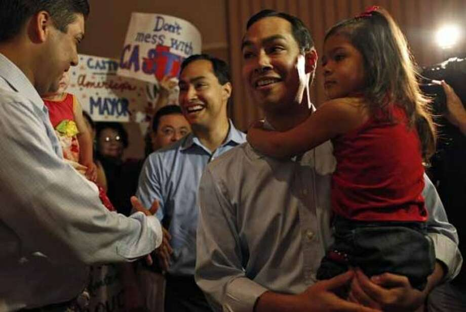 Mayor Julian Castro, right, holding his daughter, Carina, 3, and his brother, Joaquin Castro, left, greet supporters upon their arrival at the send-off party for their trip to the Democratic National Convention at the St. Paul Community Center in San Antonio on Saturday, Sept. 1, 2012. (San Antonio Express-News)