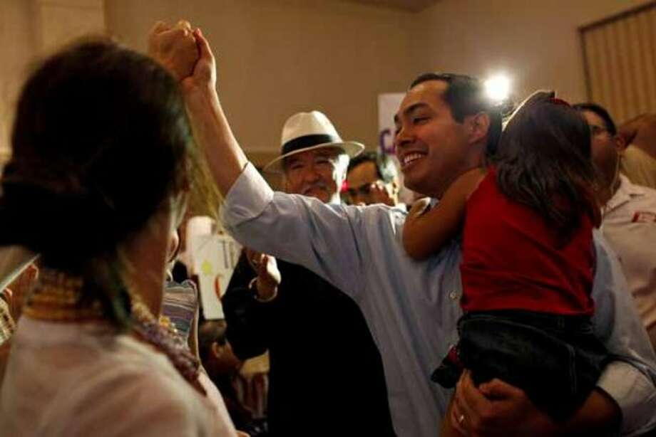 Mayor Julian Castro, right, holds his daughter, Carina, 3, as he greets supporters upon his arrival at the send-off party for his trip to the Democratic National Convention at the St. Paul Community Center in San Antonio on Saturday, Sept. 1, 2012. (San Antonio Express-News)
