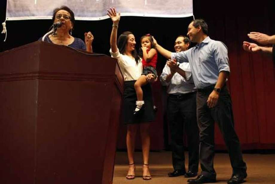 Choco Meza, left, introduces the Castro family including Mayor Julian Castro, center, his wife, Erica Castro, their daughter, Carina, 3, and his brother, Joaquin Castro, right, during the send-off party for their trip to the Democratic National Convention at the St. Paul Community Center in San Antonio on Saturday, Sept. 1, 2012. (San Antonio Express-News)