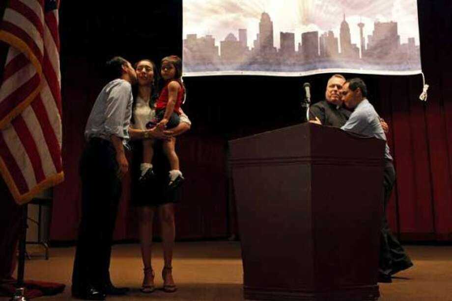 Mayor Julian Castro kisses his wife, Erica, with their daughter, Carina, 3, as his brother, Joaquin Castro, right, embraces Father Jimmy Drennan during the send-off party for their trip to the Democratic National Convention at the St. Paul Community Center in San Antonio on Saturday, Sept. 1, 2012. (San Antonio Express-News)