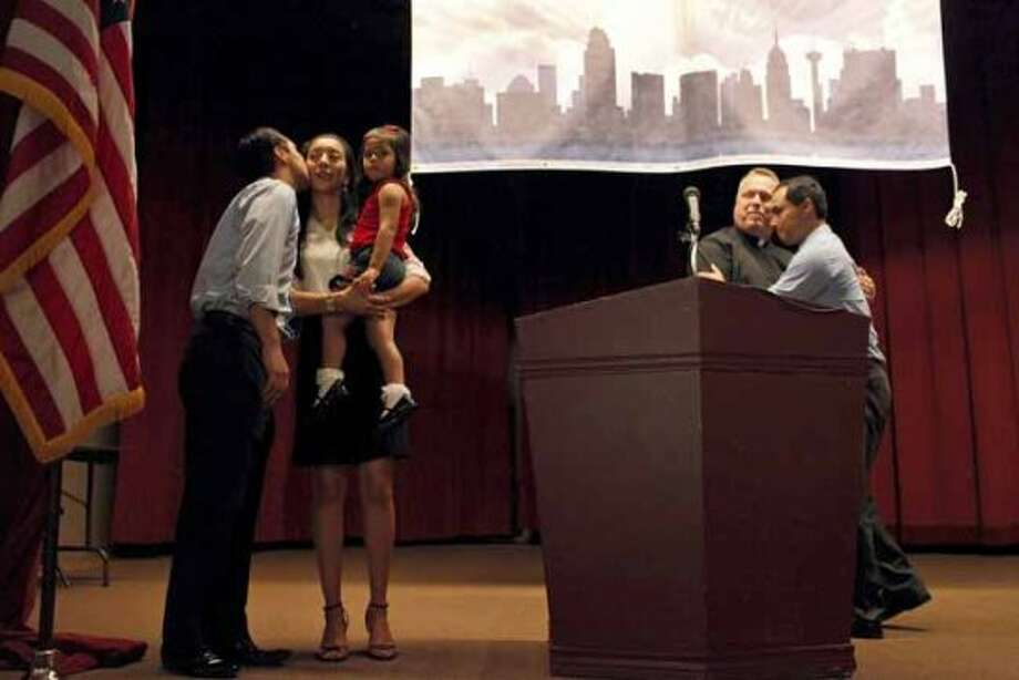 Mayor Julian Castro kisses his wife, Erica, with their daughter, Carina, 3, as his brother, Joaquin Castro, right, embraces Father Jimmy Drennan during the send-off party for their trip to the Democratic National Convention at the St. Paul Community Center in San Antonio on  Sept. 1, 2012. Castro delivers the convention's keynote address Tuesday, a nod to the importance of Hispanic voters in the race.  (AP Photo/San Antonio Express-News, Lisa Krantz) (Associated Press)