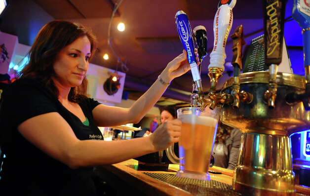 Employee Danielle Costello fills a pitcher of beer at Porky's bar on Center Street in downtown Shelton, Conn. on Tuesday September 26, 2012. Photo: Christian Abraham / Connecticut Post