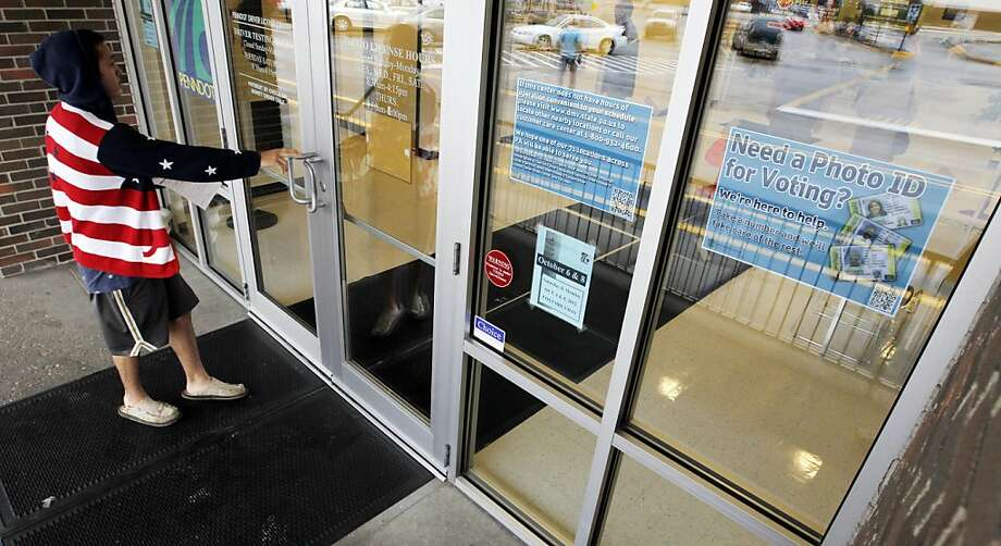 A man heads into a Pennsylvania driver's-license center that displays a sign telling of the requirement for voters to show an acceptable photo ID. Photo: Keith Srakocic, Associated Press
