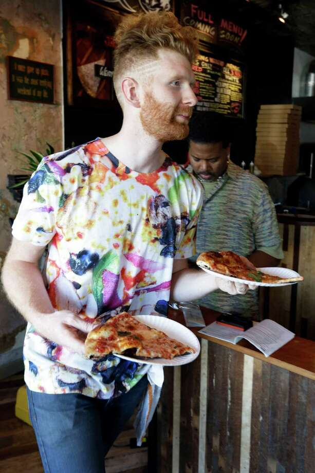 In this Wednesday, Sept. 12, 2012 photo, Brian Dwyer serves up a costumer's order at Pizza Brain in Philadelphia. Hundreds of people turned out for the grand opening of Pizza Brain this month in Philadelphia's Fishtown neighborhood. It's a restaurant where visitors can eat a slice or two of artisan pie while gawking at a pizza-related photos, records, knickknacks and videos.  (AP Photo/Matt Rourke) Photo: Matt Rourke