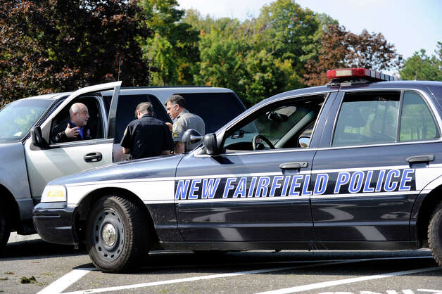 New fairfield First Selectman John Hodge talks with police in the New Fairfield High School driveway. New Fairfield and state police are investigating a fatal shooting on Meeting House Hill Circle. Sources say a man shot his son, who was allegedly breaking into a relative's house. Photo: Carol Kaliff