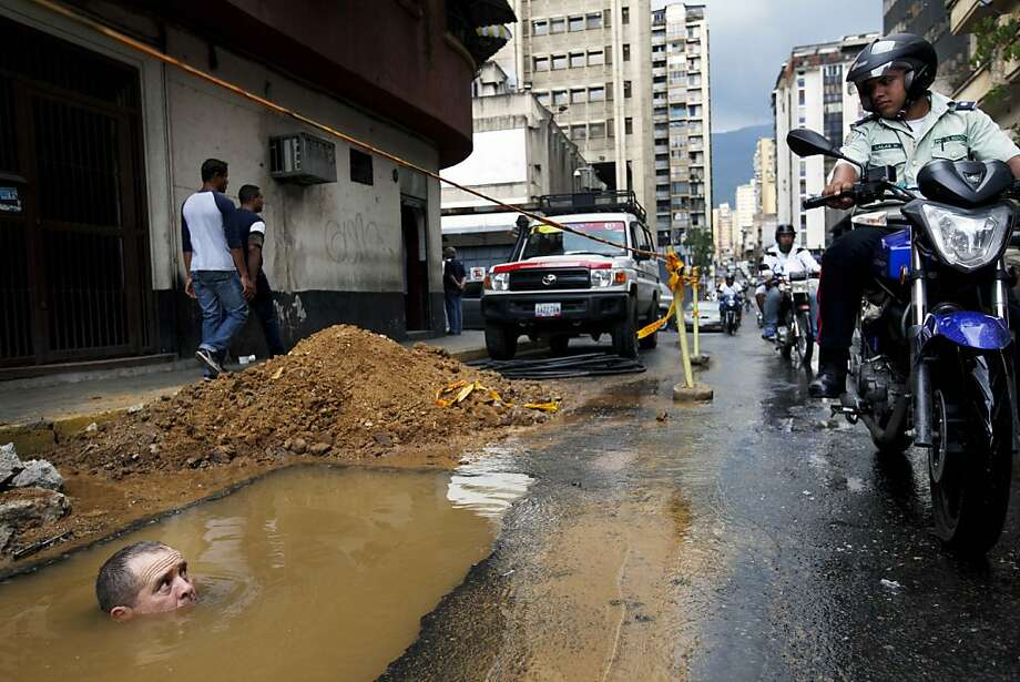 Hey, buddy, no swimming in the potholes: A Caracas policeman passes a worker trying to repair a broken underground pipe.  