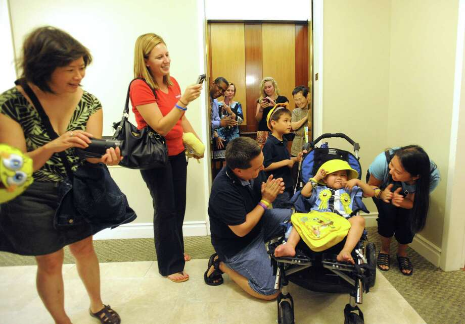 Four-year-old Alan Sanders is encouraged by his parents, Harold and Judy Sanders, after being rolled out of an elevator at the Weston Centre on Thursday, Sept. 27, 2012. Alan's wish to press all the buttons in the elevator of a tall building was granted by the Make-A-Wish Foundation, which worked with Weston Centre management to make Alan's dream come true. People that work in the building greeting him with streamers and cheers each time the door opened on a different floor. Photo: Billy Calzada, Special To The Express-News / © 2012 San Antonio Express-News