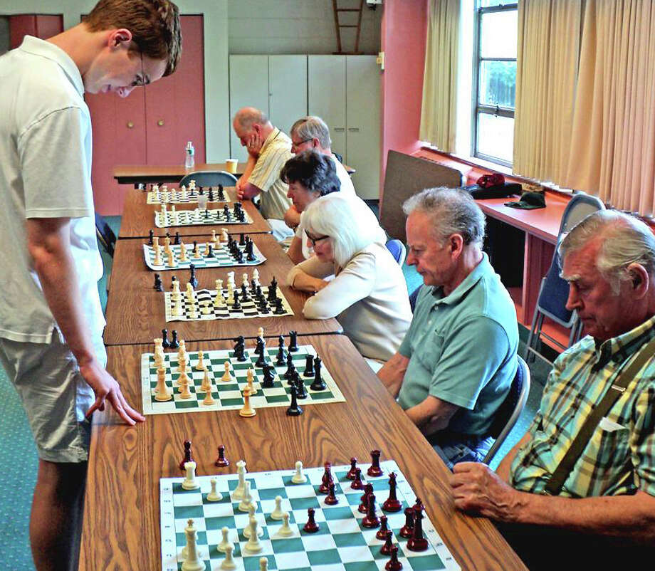 Michael Finneran, standing, contemplates his next move against Ron Hirsch in one of several recent matches he played at the Fairfield Senior Center. The recent Ludlowe grad and former state chess champion played six chess club members simultaneously. From back to front are: Frank DeStefano, Roy Gosse, Loretta Loomie, Betty Holm, Hirsch and Teo Perini. Photo: Ron Atwater / Fairfield Citizen contributed