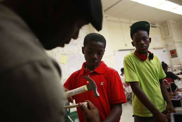 Teacher Jahi helps his students Gamoni Polk, 12, and Jeremiah Lester, 14, build a drum during Manhood Development class at Edna Brewer Middle School on Wednesday Sep. 12, 2012 in Oakland, Calif. Photo: Mike Kepka, The Chronicle
