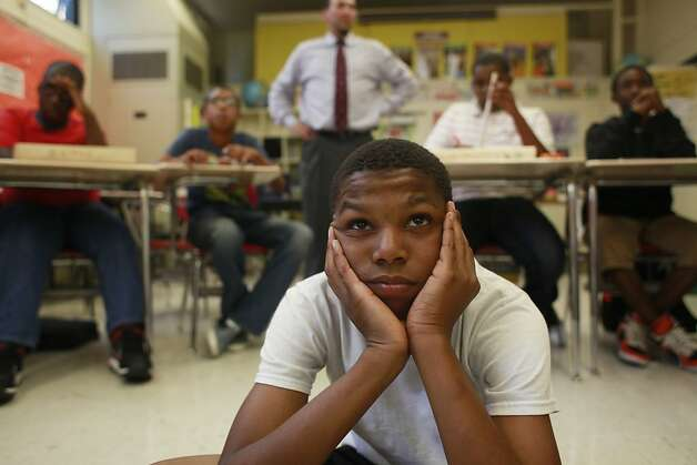 Ahjae Johnson, 12, of Edna Brewer Middle School in Oakland watches his instructor show how to make a drum during manhood development class, which seeks to prevent suspensions by giving students focus. Photo: Mike Kepka, The Chronicle