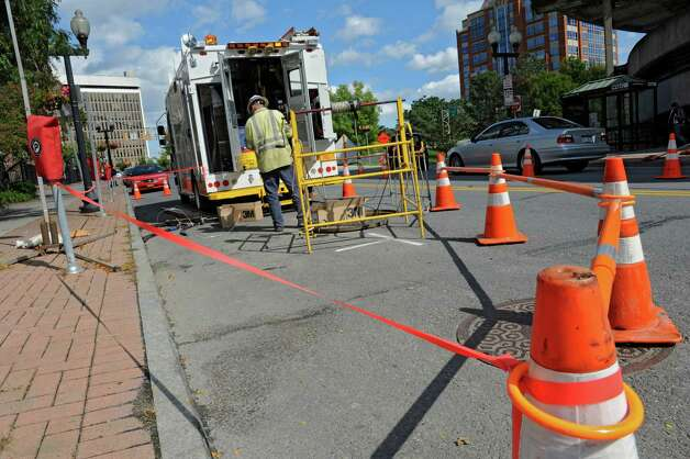 A National Grid employee works at a manhole on North Pearl St. on Thursday, Sept. 27, 2012 in front of Cap Rep where another manhole cover incident took place Wednesday evening in Albany, N.Y. (Lori Van Buren / Times Union) Photo: Lori Van Buren