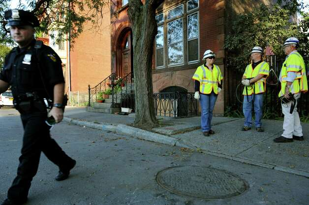 National Grid workers stand near the replaced manhole cover on Thursday, Sept. 27, 2012, on Fifth Street in Troy, N.Y. The cover blew from arcing wires. (Cindy Schultz / Times Union) Photo: Cindy Schultz