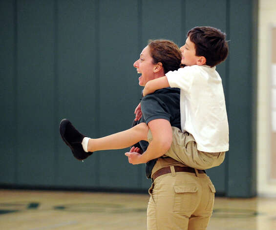 With her son Harrison, 7, on her back, Greenwich Academy volleyball coach Christy Girard cheers on her team during the Girls high school volleyball match between Greenwich Academy and King at Greenwich, Thursday, Sept. 27, 2012. Photo: Bob Luckey / Greenwich Time